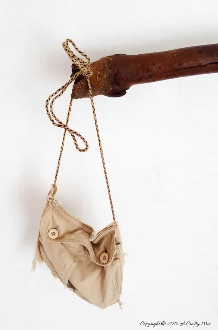 Hang a small pocket hand bag from the end to store all those bathroom goodies. #DIYHomeDecor #Branchtowelrack #branchrepurpose #DIYTutorial #DIYBathroomdecor #Acraftymix
