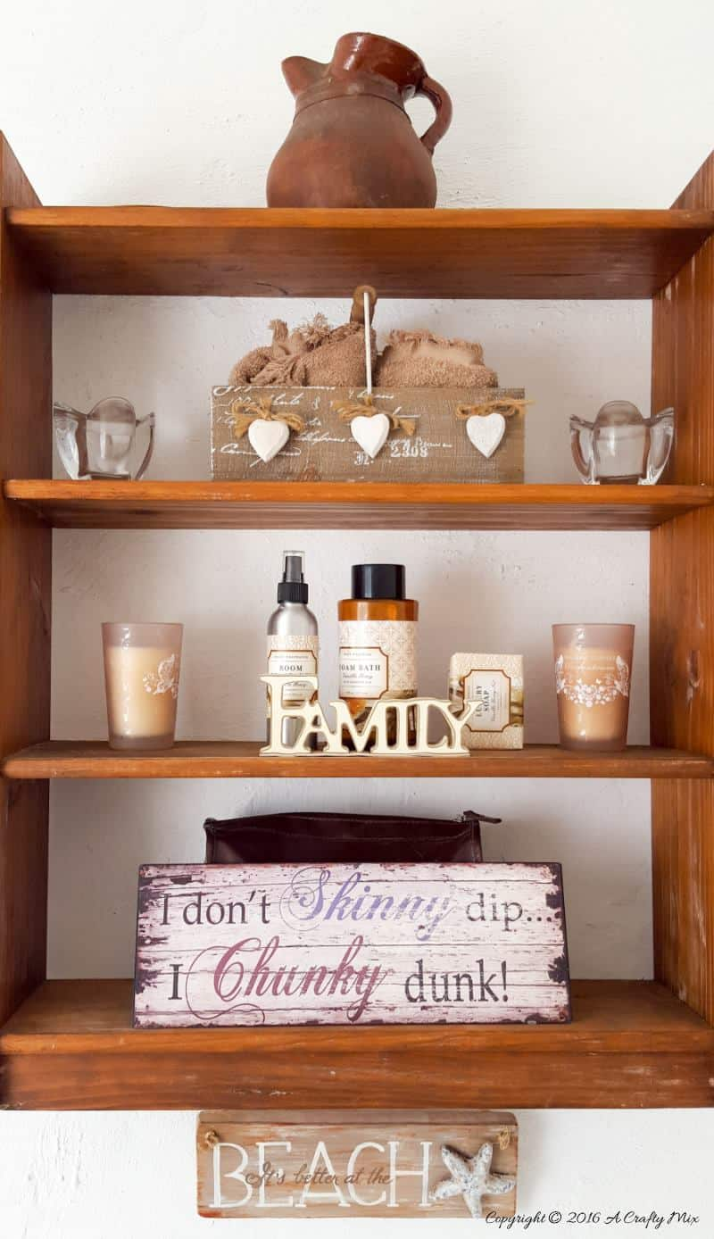 A thrifted shelf hung on the wall holds all our bathroom accessories #ACraftymix #StorageSolutions #SmallSpace