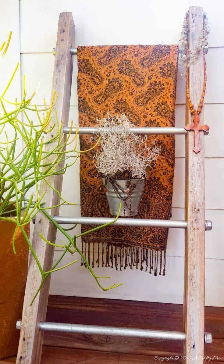 A throw and a little plant make a lovely statement on this easy to make industrial chic storage ladder #creativestorage #displayladder #industrialchic #storageladder