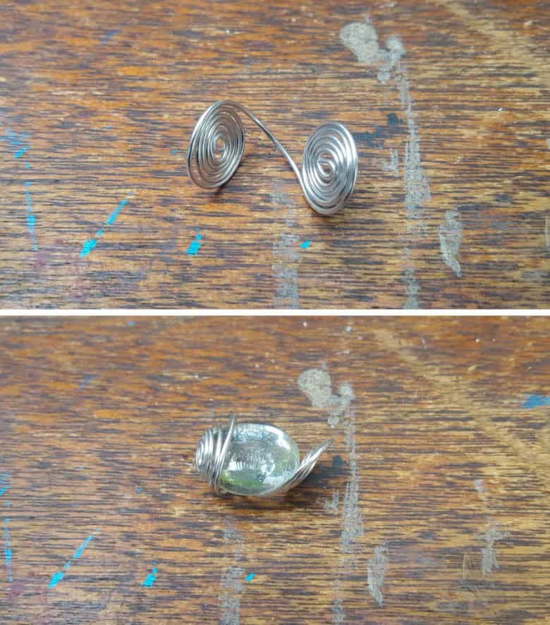 Bend the two ends of the curled wire upwards and place the glass bead inside and wrap the edges up to enclose the glass bead.