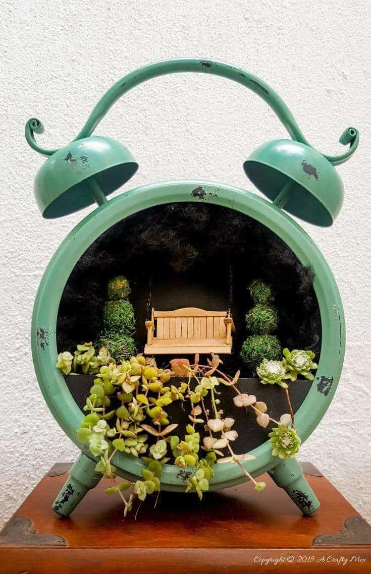 The cutest little fairy garden inside a clock. Includes full plans for making the porch swing and the miniature topiary trees #IndoorGardening #FairyGarden #ClockRepurpose