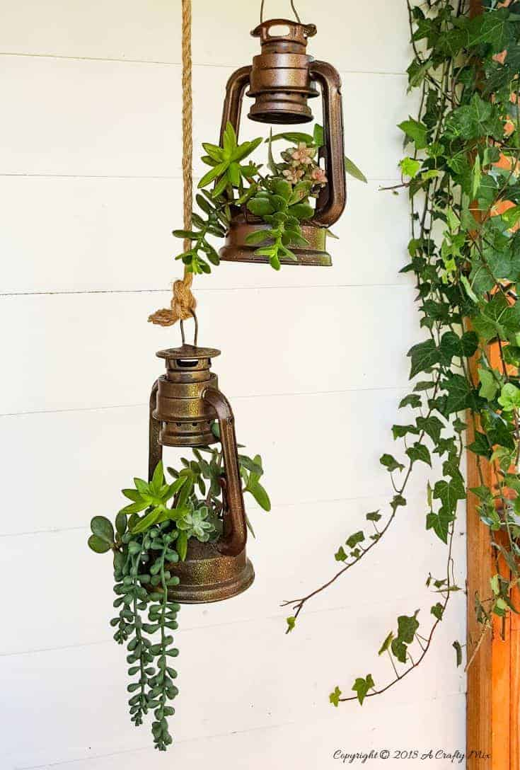 These charming old school lantern planters look amazing hanging from an antique pulley.  See how to make your own with this super tutorial. Include how to turn lanterns into planters #DIYHomeDecor #Planters #farmhousestyle #DIYPlanters #DIYHangingPlanter #UpcycledPlanter #ACraftyMix #LanternPlanters