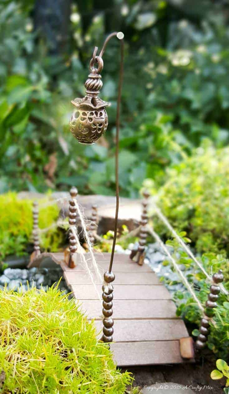 Recycle an empty plastic container and make and this adorable fairy bridge for your fairy garden #gardenideas #fairygarden #cupcycle #upcycle #repurpose #plasticrecycle #plasticcontainer