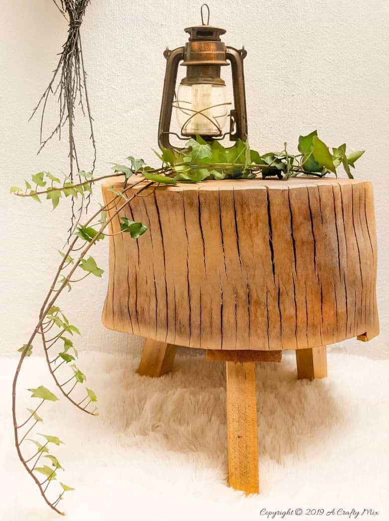 Gorgeous tree stump stool with ivy and an old lantern