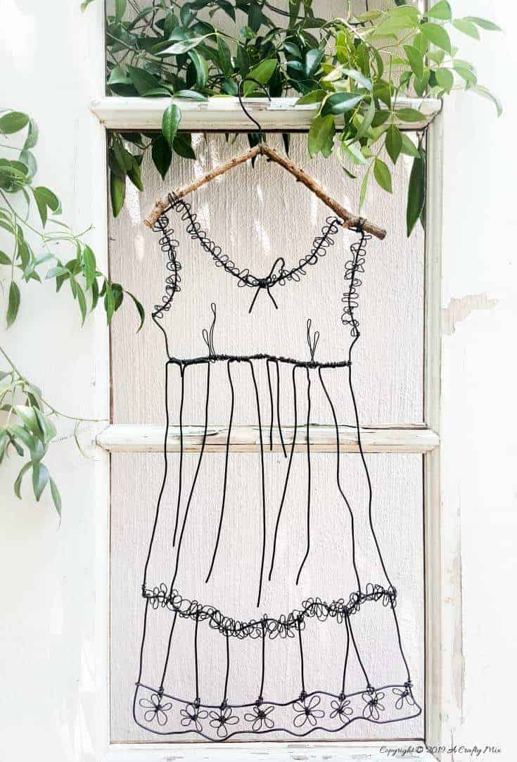 Add little elegance and whimsy to your wall art with this DIY wire dress tutorial. Made from jewelry wire, it's rustic and fun to do. Includes dress template and instructions for printing. Can be hung indoors or out. #WireArt #DIYTutorial #ACraftyMix #WallDecor