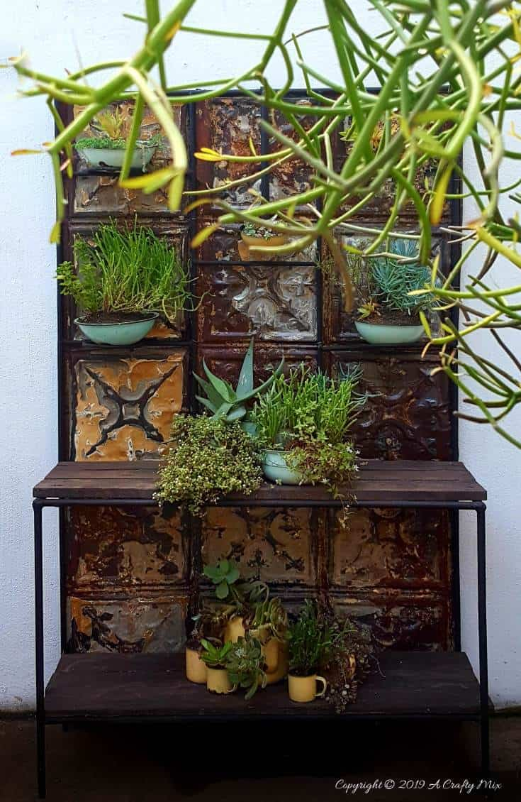 How to makeover an old plant stand using ceiling rusty tin ceiling tiles. Includes 3 ways to clean and prepare the tiles for craft projects #tinceilingideas #tinceilinghomedecor #tinceilingtilesrepurposed #plantstandideas #ACraftyMix
