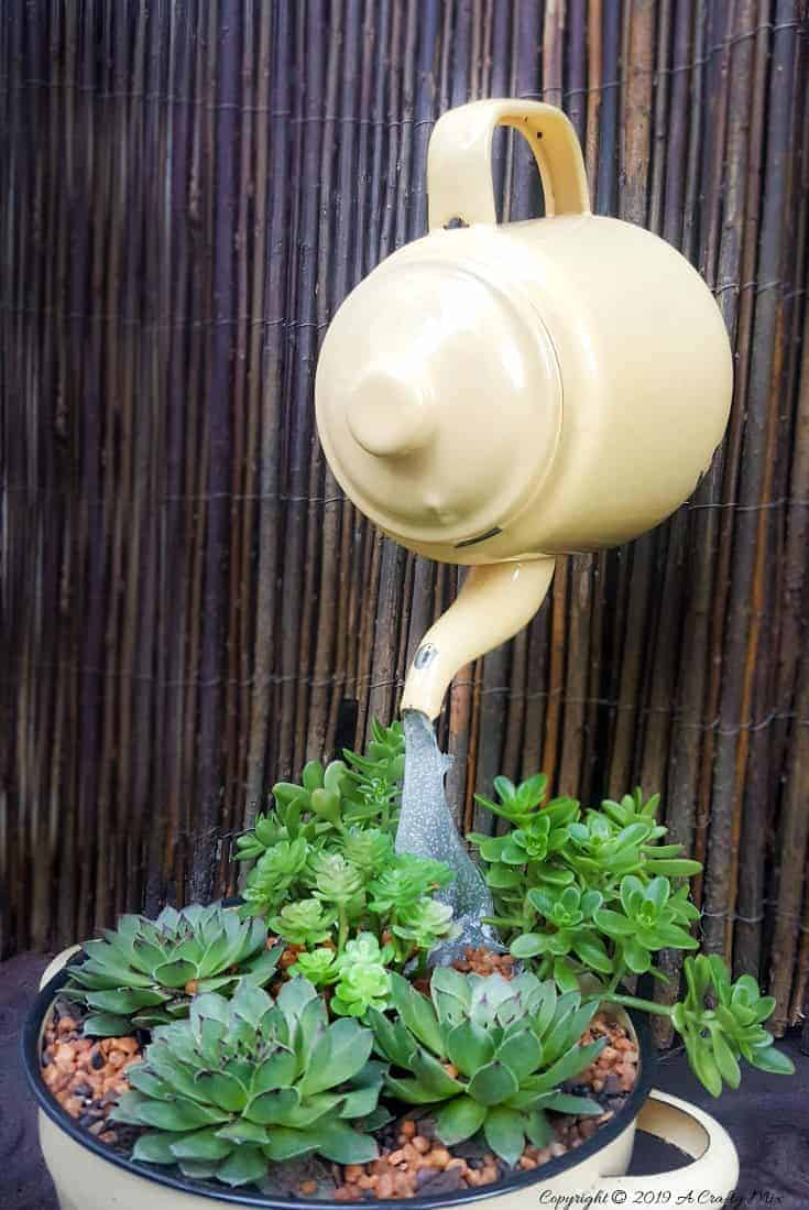 """Love the way the """"water"""" seems to flow from the floating teapot into the succulents. Come see how to make your own #SucculentPlanter #FloatingTeapot #ACraftyMix #DIYTutorial #ForkRepurpose #CrazyCrafts"""