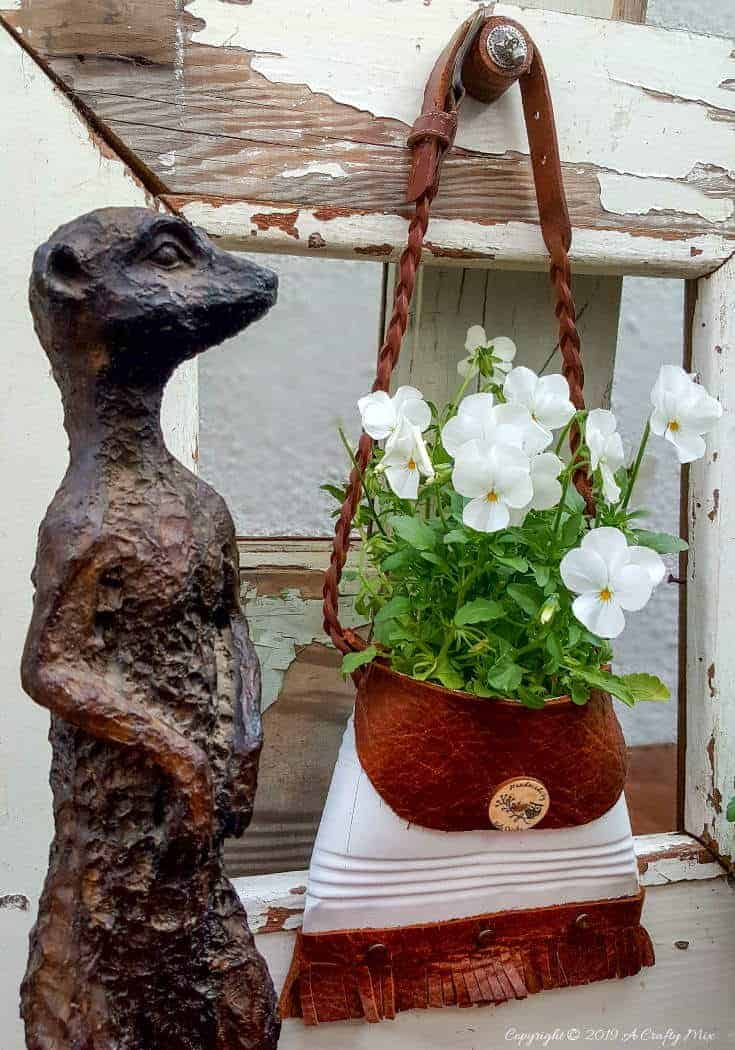 A close up of the meerkat and the tin can with pansies. So cute #tincan #recycle #repurpose #tincanrecycle #tincanplanter #acraftymix #creativetincanprojects #uniquetincanDIY