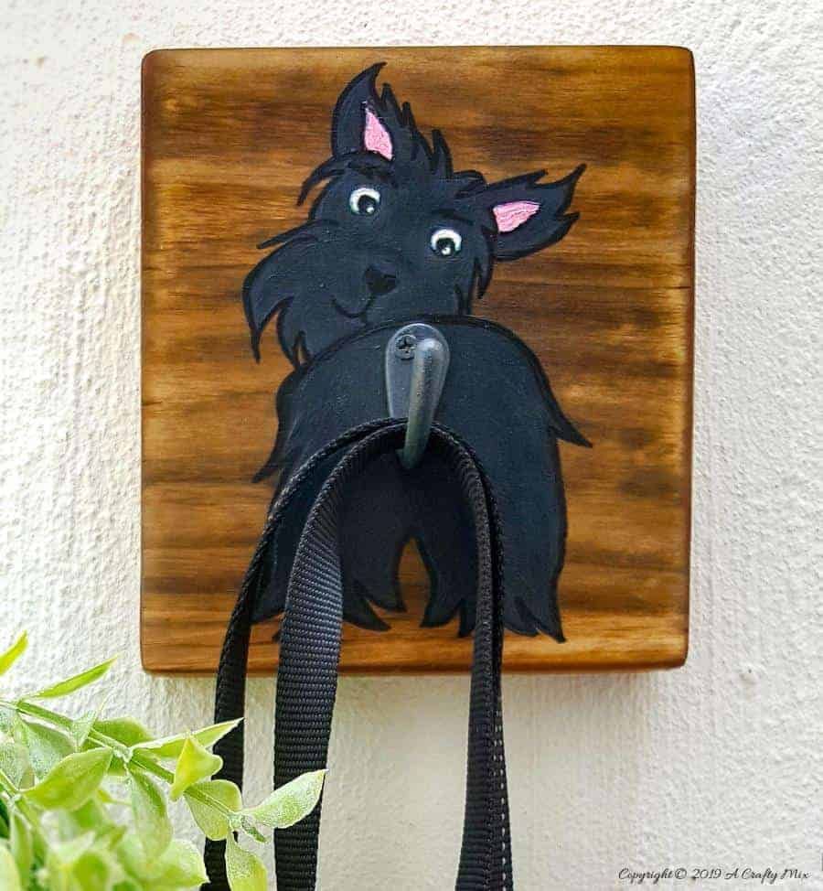 Make an adorable and easy DIY Dog Leash holder using a scrap piece of wood and craft paint. You and your fur baby will love it and the tutorial includes a free printable! #DIYDogLeash #Leashholderideas #WoodLeashHolder #ACraftyMix #FreePrintable #ScottishTerrier #PetLeashHolder #DIYLeashHolder