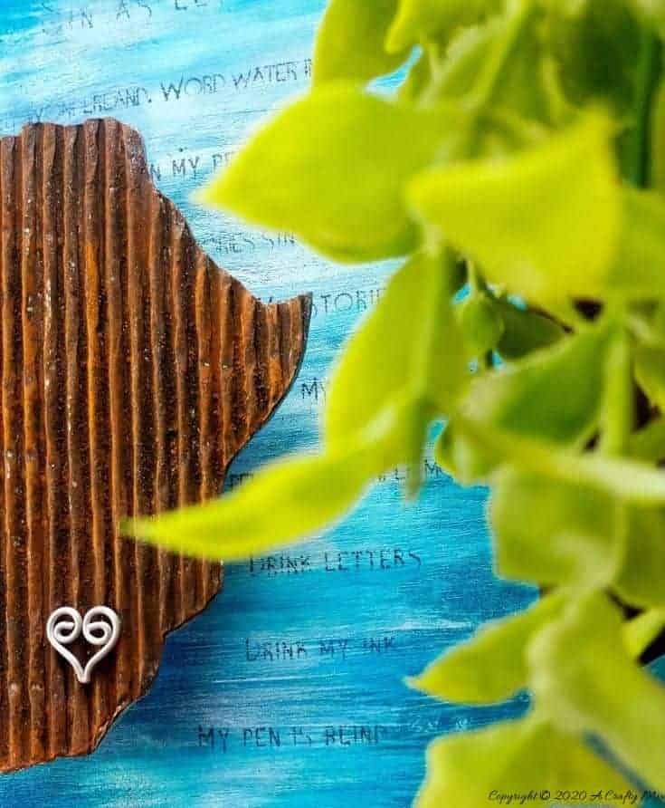 Mixed media pieces are always fun to put together and the possibilities are endless. This tutorial will show you how to make cardboard look like a rusty sheet of metal and turn your mixed media into a night light. #mixedmedia #mixedmediatutorial #DIYNightLight #ACraftyMix #fauxrust #Africa #HomeDecor