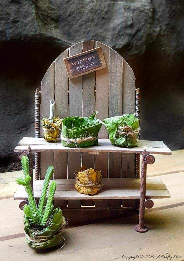 Make this adorable fairy potting bench using rusty nails and stirrer sticks. Quick and easy craft idea for your miniature garden #FairyPottingBench #FairyDIYCrafts #ACraftyMix #FairyGardens #FairyCrafts #WhimsicalFairyCrafts #SimpleFairyCrafts #MiniaturePottingBench #RustyNails