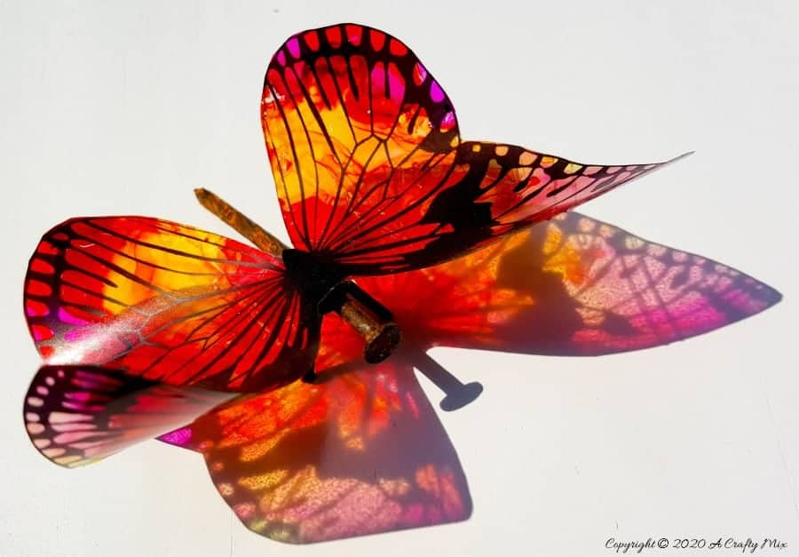 Rusty nails have never looked more beautiful with these translucent butterfly wings. Full tutorial includes 2 free printables to make the butterfly wings and/dragonfly wings. #DragonflyWingsTemplate  #DragonflyWingsDIY #ButterflyWings #ACraftyMix #DIYDragonfltWings #AlcoholInkCrafts #AlcoholInk #CraftTutorial