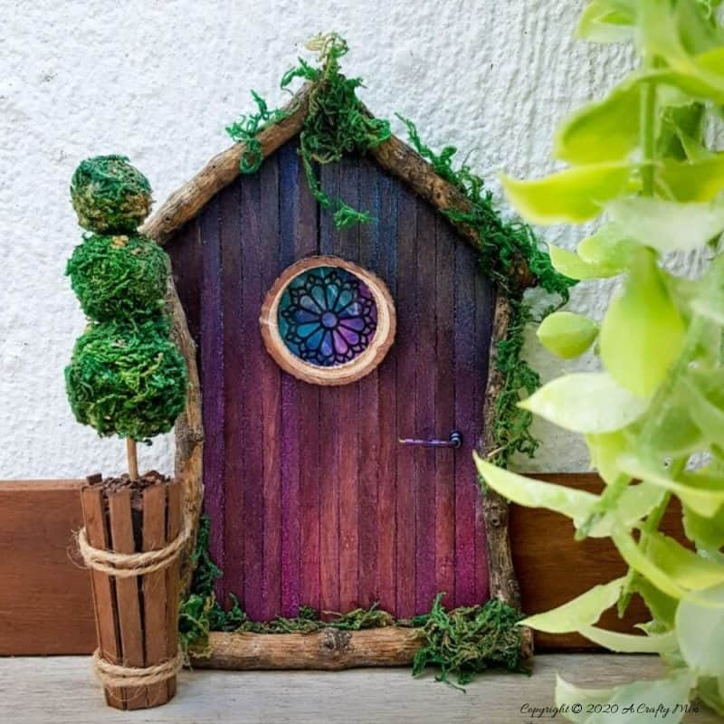 Welcome the fae folk into your home with this gorgeous stained glass fairy door. Made with things you probably already have in your craft cupboard the door doubles up as a night light. #FairydoorDIY #FairyDoorIdeas #ACraftyMix #MakeAFairyDoor #MiniatureStainedGlass #AlcoholInk
