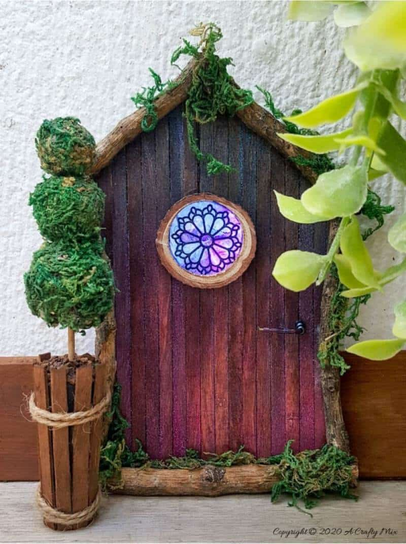 Welcome the fae folk into your home with this gorgeous stained glass fairy door. Made with things you probably already have in your craft cupboard, the door doubles up as a night light. #FairydoorDIY #FairyDoorIdeas #ACraftyMix #MakeAFairyDoor #MiniatureStainedGlass #AlcoholInk