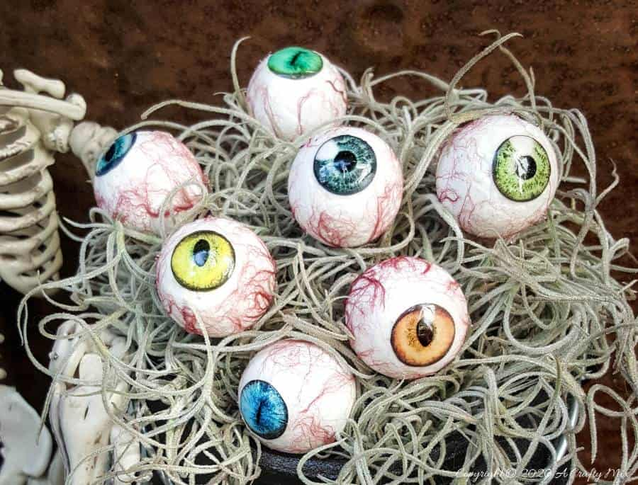 """Up the creepy stakes this Halloween and make these realistic eyeballs for Halloween. Quick and budget-friendly they'll add just the right spooky factor to your decor. The tutorial includes free """"iris"""" printables to use #HalloweenDecor #CreepyEyeballs #ACraftyMix #FreePrintables"""
