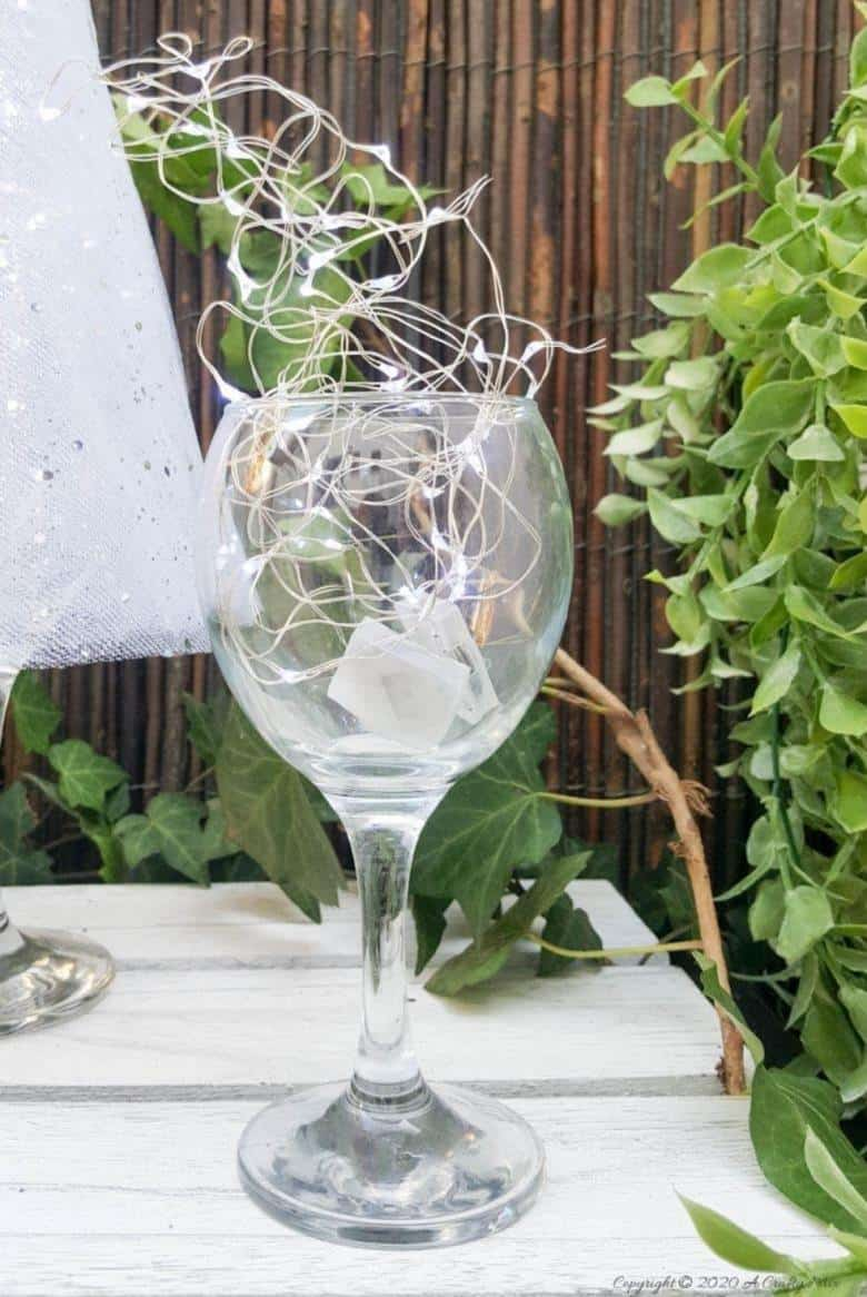 Insert fairy lights into the goblet of the wine glass and switch them on