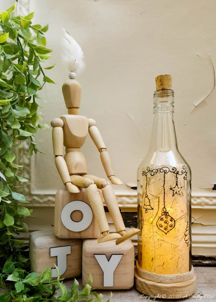 Take your glass bottle light to a whole new level with this DIY idea. A quick and easy way to repurpose and customize ONE bottle to fit any occasion or season with swappable art inserts. And you'll have loads of fun coming up with new images to put inside too. #bottlelight #winebottlelights #acraftymix #bottlerepurpose #bottlecrafts