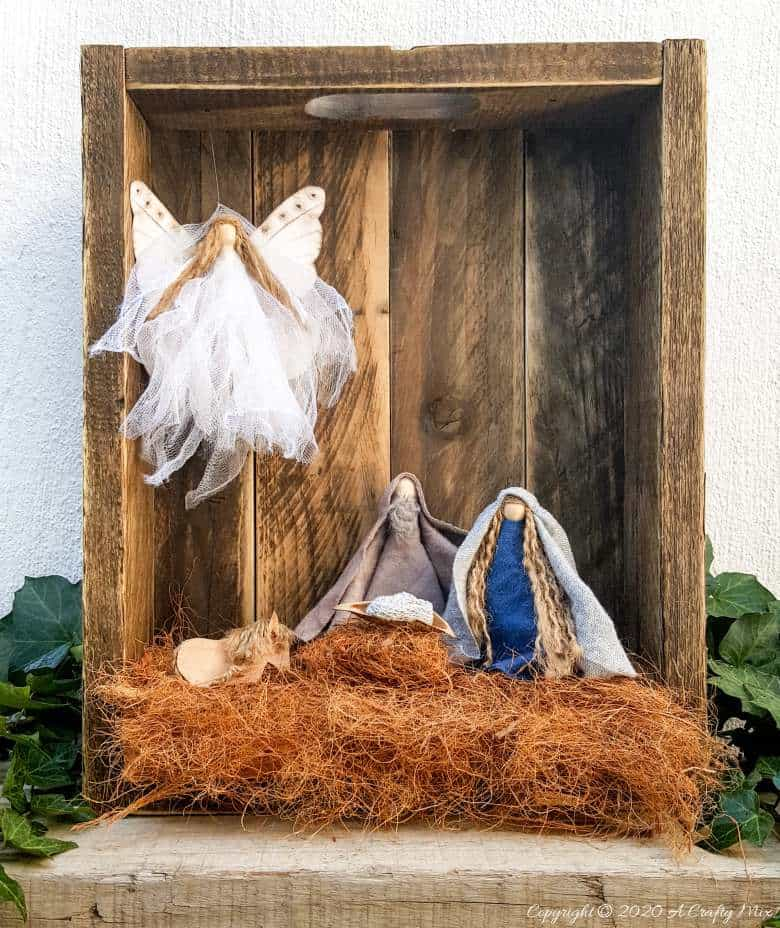 """This easy to follow tutorial with show you how to make a rustic clothespin Nativity scene out of fabric scraps and wooden pegs. The tutorial includes a """"free to download"""" printable for the angel wings. #ClothesPinCrafts #DIYNativity #WoodenPegCrafts #ACraftyMix #ChristmasCrafts #NativityScene"""