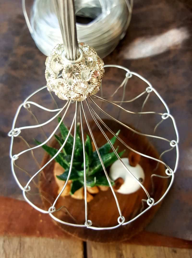 A beautiful crystal bead sits on top of the birdcage. This easy to follow tutorial will show you how to make your own art deco wire bird cage. Made in a morning, it's a fun way to add a little handcrafted glamour to you décor. #BirdCage #DIY #ACraftyMix