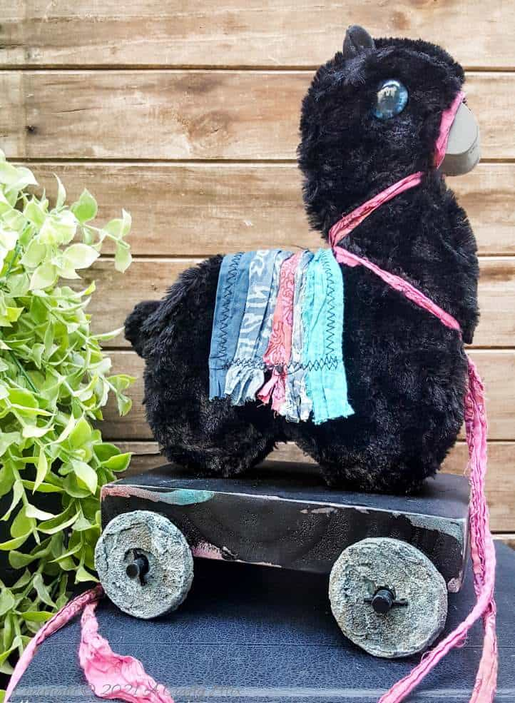 In the tradition of old toys we made this DIY Pull Toy llama using upcycled tin can wheels. This fun recycled craft idea comes with a free printable llama template. #Upcycle #TinCan #ACraftyMix #PullToy #HomeDecor