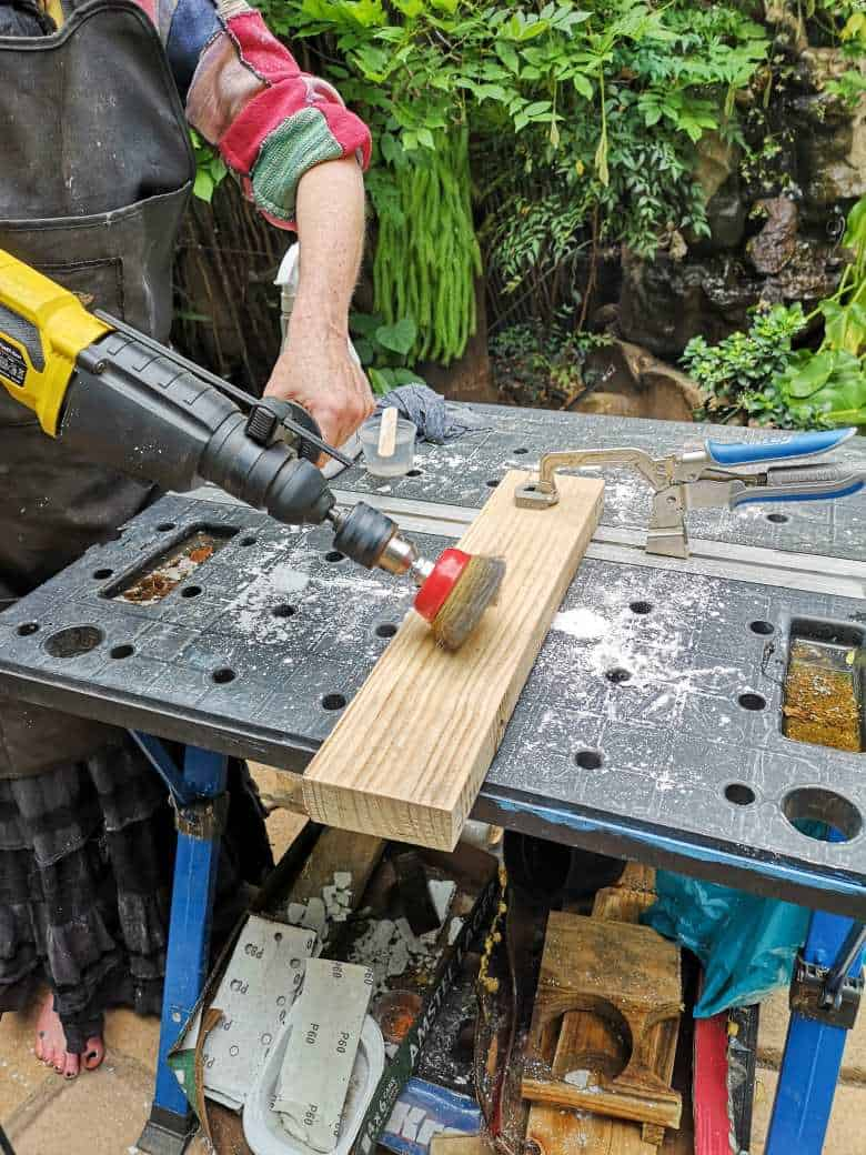 Using a metal brush attached to a drill to distress the frame