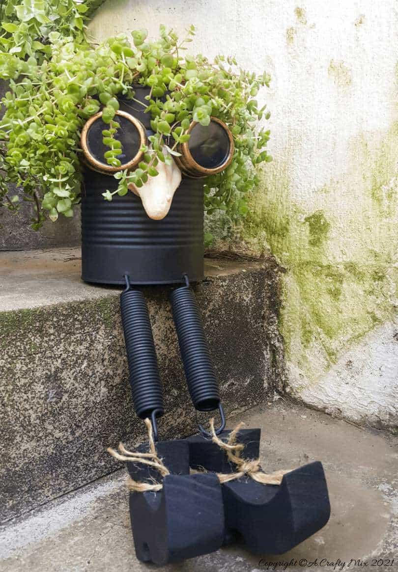 Looking for a creative way to repurpose a tin can? The you'll love this steampunk tin can planter. We call him Dr Edinose and he's sure to add a little whimsy to your outdoor decor. #steampunkplanter #ACraftyMix #TinCanRecycle