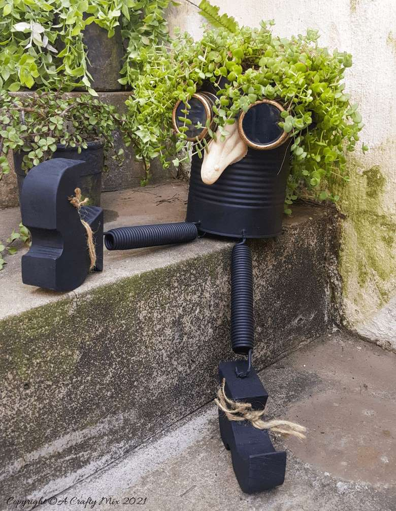 Looking for a creative way to repurpose a tin can? The  you'll love this tin can steampunk planter. We call him Dr Edinose and he's sure to add a little whimsy to your outdoor decor. #steampunkplanter #ACraftyMix #TinCanRecycle